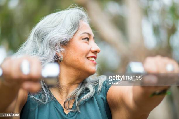 senior mexican woman lifting weights fitness - fat old lady stock photos and pictures