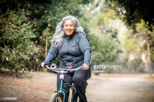 senior mexican woman riding bicycle - mature adult stock pictures, royalty-free photos & images