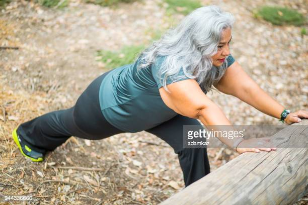 senior mexican woman stretching legs - chubby legs stock photos and pictures