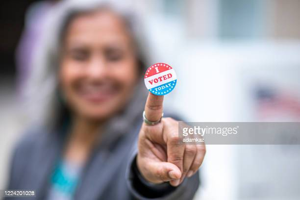 senior mexican woman with i voted sticker - adamkaz stock pictures, royalty-free photos & images