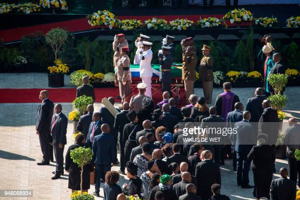 Senior military officials salute as they stand by after carrying the coffin of Winnie Madikizela-Mandela into Orlando Stadium in Soweto for a funeral...