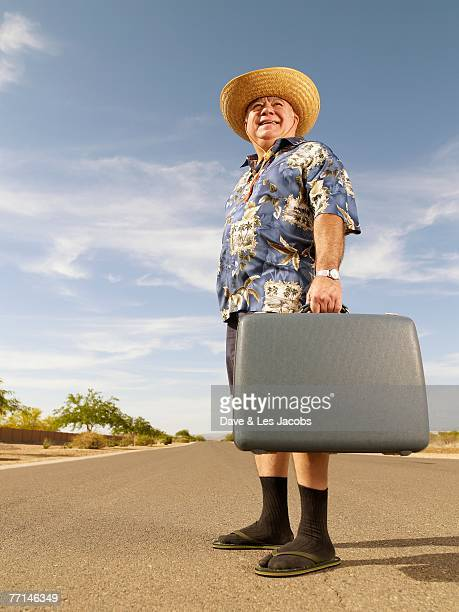 senior mixed race man holding suitcase - sandal stock pictures, royalty-free photos & images