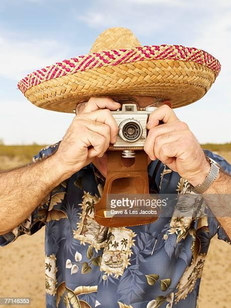 Senior Mixed Race man taking photograph