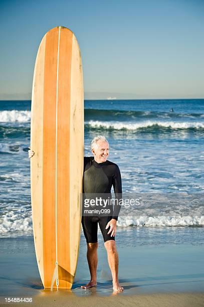 senior model posing with wooden surfboard