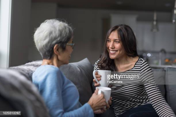 Senior mom and her adult daughter enjoy a cup of coffee together