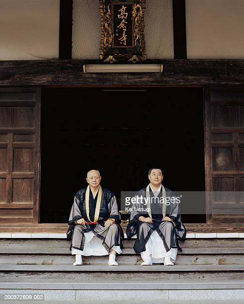 Senior monk and mature monk sitting on steps of temple, portrait
