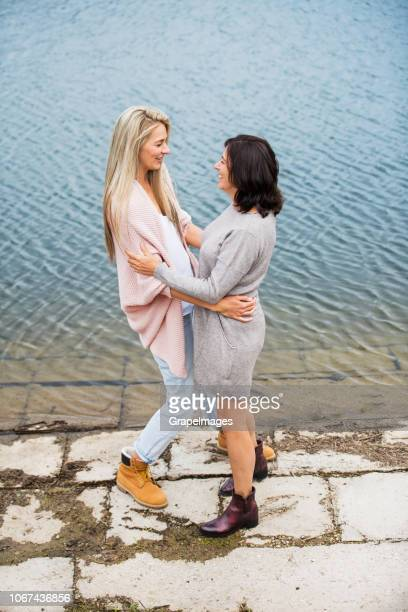 a senior mother and adult daughter standing by the water reservoir in nature, looking at each other. - dress over pants stock pictures, royalty-free photos & images