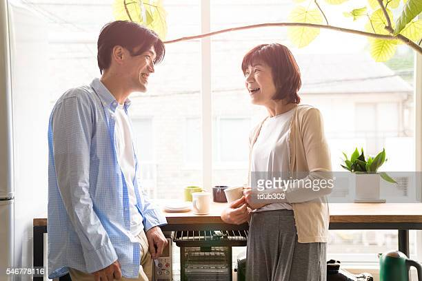 senior mother and adult son talking in the kitchen - japan mom and son stock photos and pictures