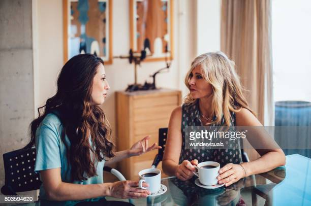 senior mother and daughter drinking coffee together at home - talking stock pictures, royalty-free photos & images
