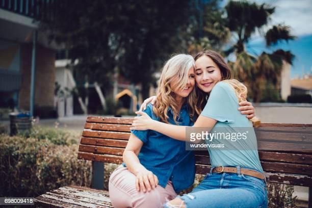 Ältere Mutter und Tochter umarmt sitzend auf einer Bank