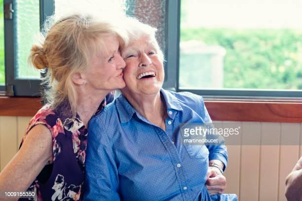 Senior mother and daughter having tender moment in summer house.