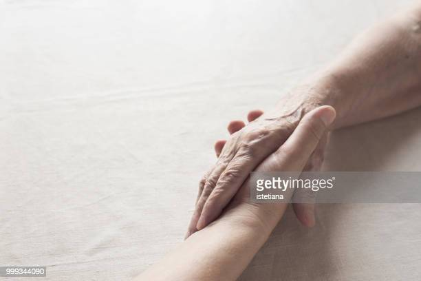 senior mother and daughter holding hands - holding hands stock pictures, royalty-free photos & images