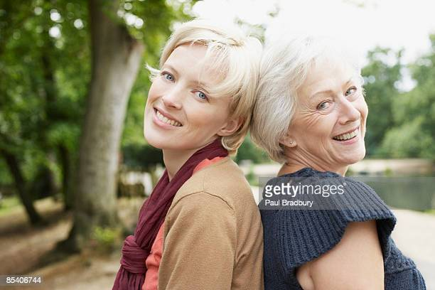 Senior mother and daughter near pond