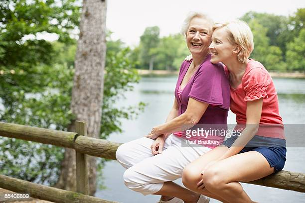 Senior mother and daughter sitting near pond
