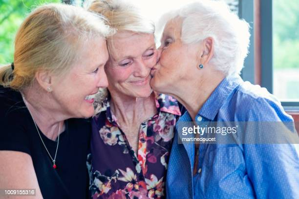Senior mother and daughters having tender moment in summer house.