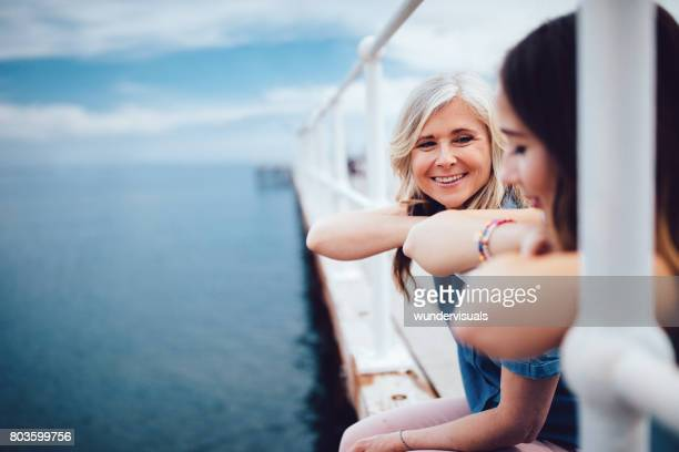 Senior mother and teenage daughter relaxing together on a pier