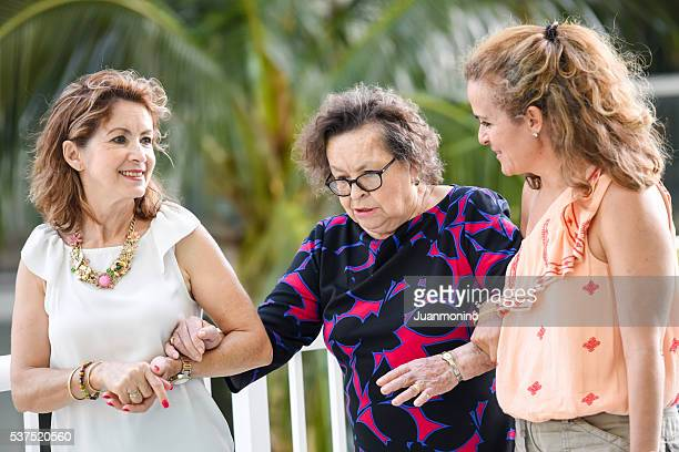 Senior mother being helped to walk by her mature daughters