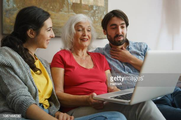senior mother using laptop with daughter and son on living room sofa - girlfriend stock pictures, royalty-free photos & images