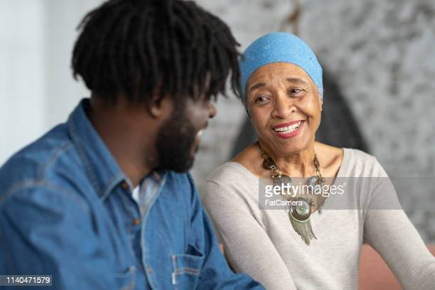 senior mother with cancer spending time with her adult son - survival stock pictures, royalty-free photos & images