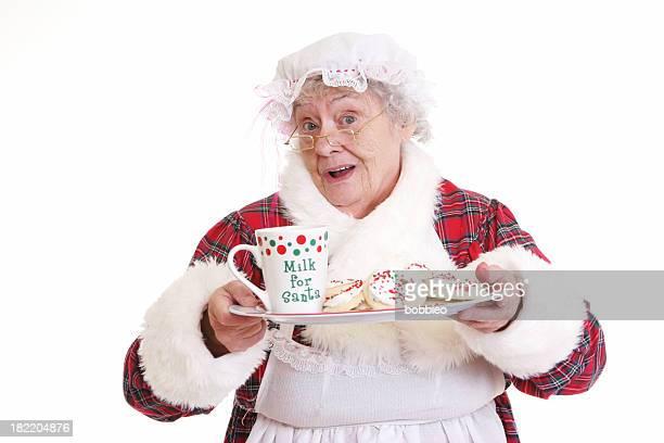 senior frau claus mit milch und kekse - weihnachtsfrau stock-fotos und bilder