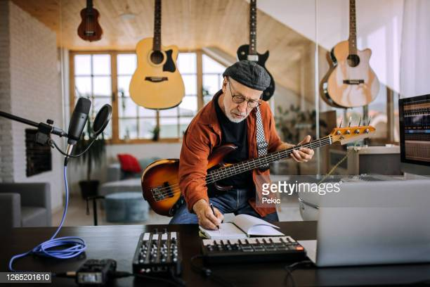 senior musician with guitar writing on a music sheet - composer stock pictures, royalty-free photos & images