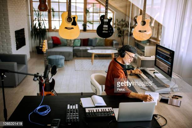 senior musician writing in his home office studio - composer stock pictures, royalty-free photos & images