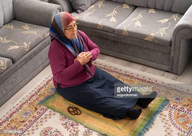 hogere moslimvrouw die thuis bidt - turkije midden oosten stockfoto's en -beelden