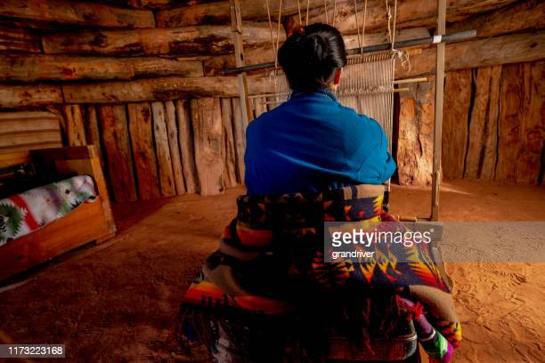 senior native american navajo woman in a traditional hogan in monument valley arizona using a loom to create a traditional indian blanket - apache stock pictures, royalty-free photos & images