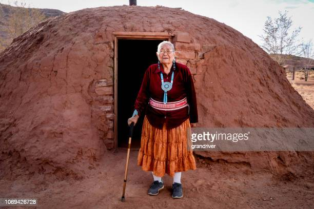 senior native american navajo woman in monument valley outside a traditional hogan - navajo hogan stock photos and pictures