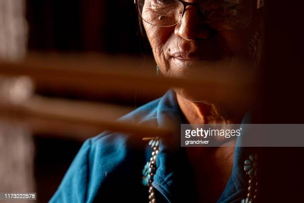 senior native american navajo woman sitting in a traditional authentic hogan using a homemade loom to create a handwoven blanket - cherokee indian women stock pictures, royalty-free photos & images