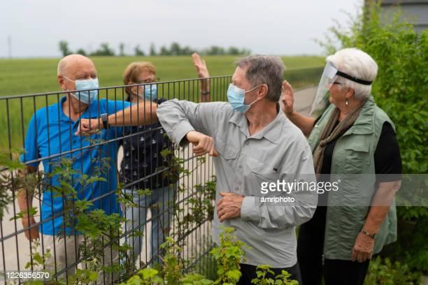 voisins aînés saluant les uns les autres par la clôture de jardin dans les temps du coronavirus - gestes photos et images de collection