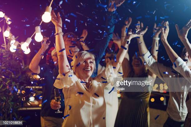 senior new year rooftop party - new year's eve stock pictures, royalty-free photos & images