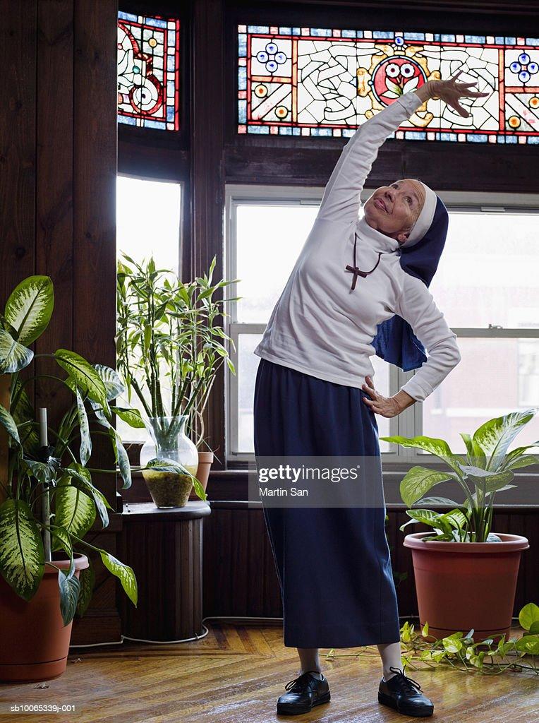 Senior nun doing exercise, looking up, smiling : Foto stock