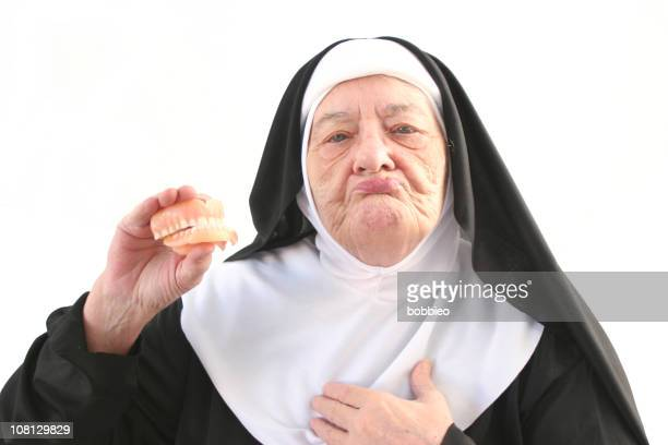 senior nun holding up dentures, isolated on white - nun stock photos and pictures
