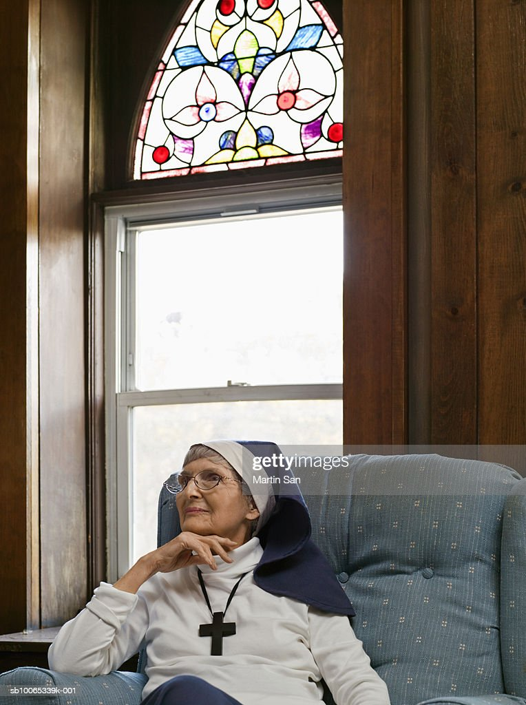 Senior nun sitting on arm chair, looking away : Foto stock