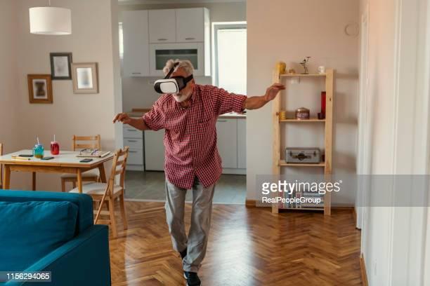 senior oude man eldery genieten van het spelen spel met vr virtual reality - real people stockfoto's en -beelden