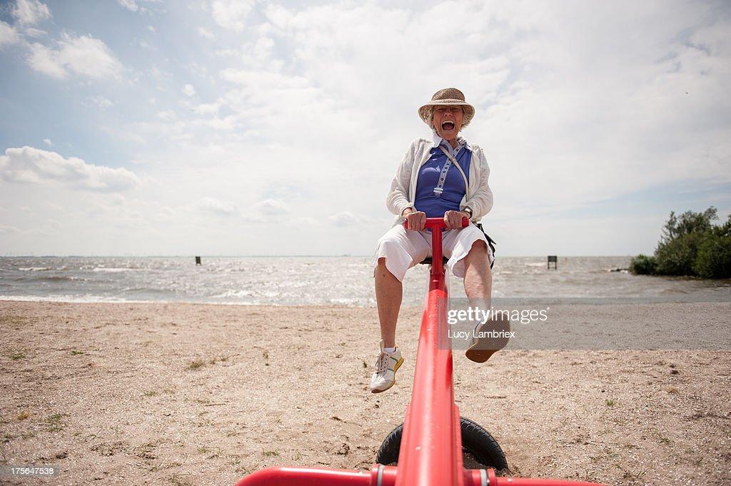 Senior on a seesaw : Stock Photo