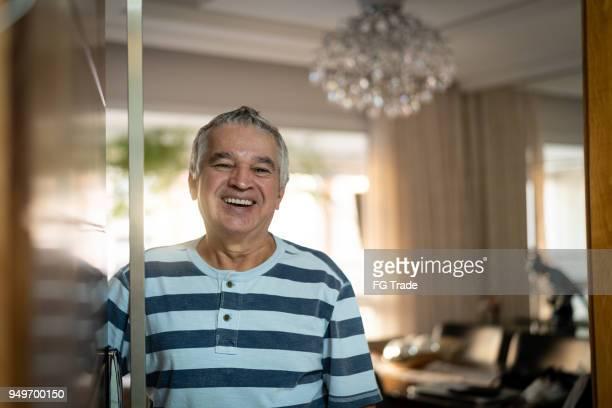 senior seine haustür öffnen - gast stock-fotos und bilder
