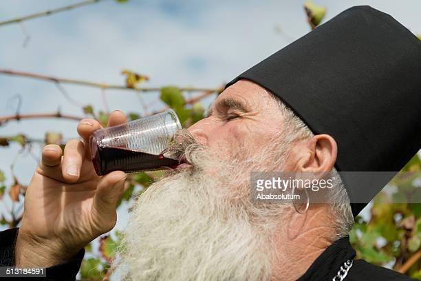 Senior Ortodox Priest Drinking Red Wine, Harvesting, Europe