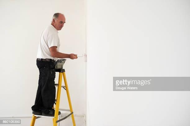 Senior painter and decorator painting room.
