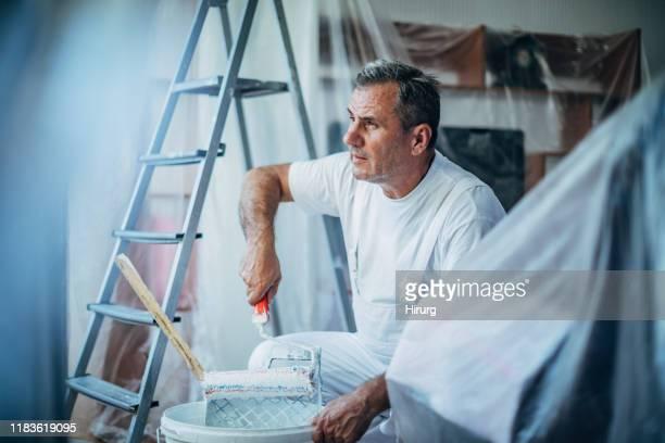 senior maler malerei wohnzimmer - maler stock-fotos und bilder