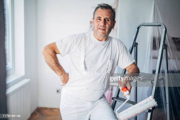 senior painter taking a break from painting - white jumpsuit stock pictures, royalty-free photos & images
