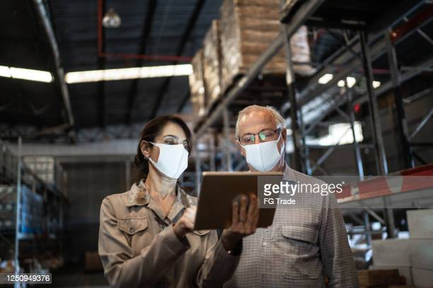 senior partners walking and using digital tablet at warehouse - with face mask - manufacturing stock pictures, royalty-free photos & images