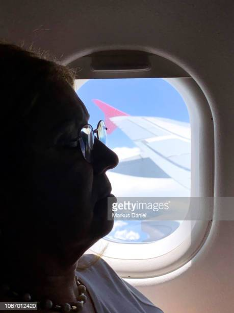 Senior Passenger in front of Airplane Window