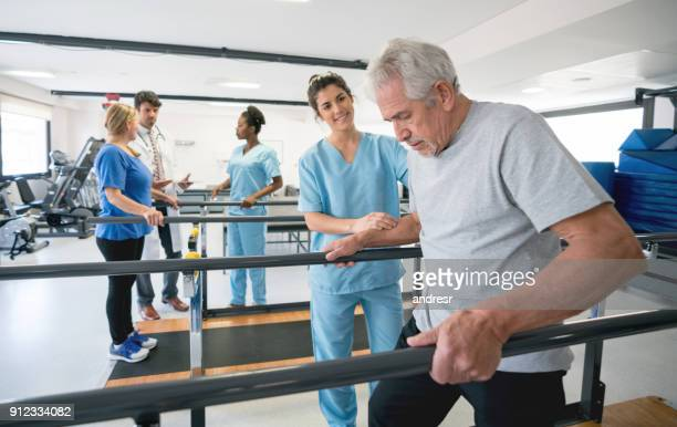 senior patient and beautiful occupational theraã­st walking between parallel bars - bounce back stock photos and pictures