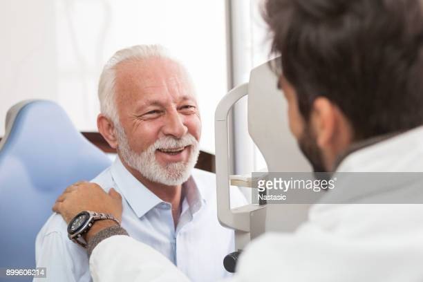 senior patient consulting with optician in office - optometry stock pictures, royalty-free photos & images