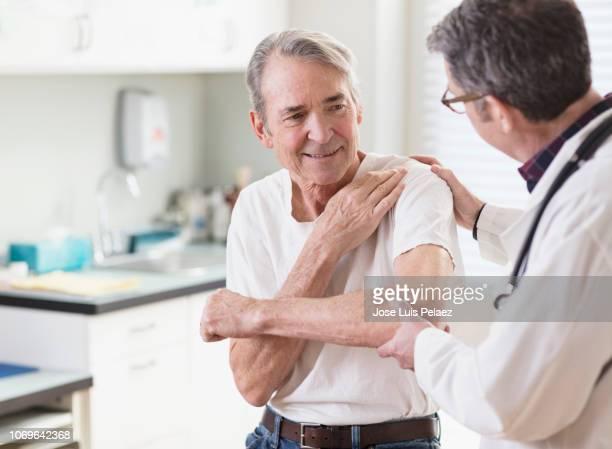 senior patient explaining shoulder pain to doctor in clinic - looking over shoulder ストックフォトと画像