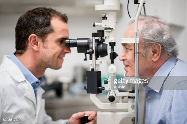 senior patient getting an eye exam at the optician - optometry stock pictures, royalty-free photos & images