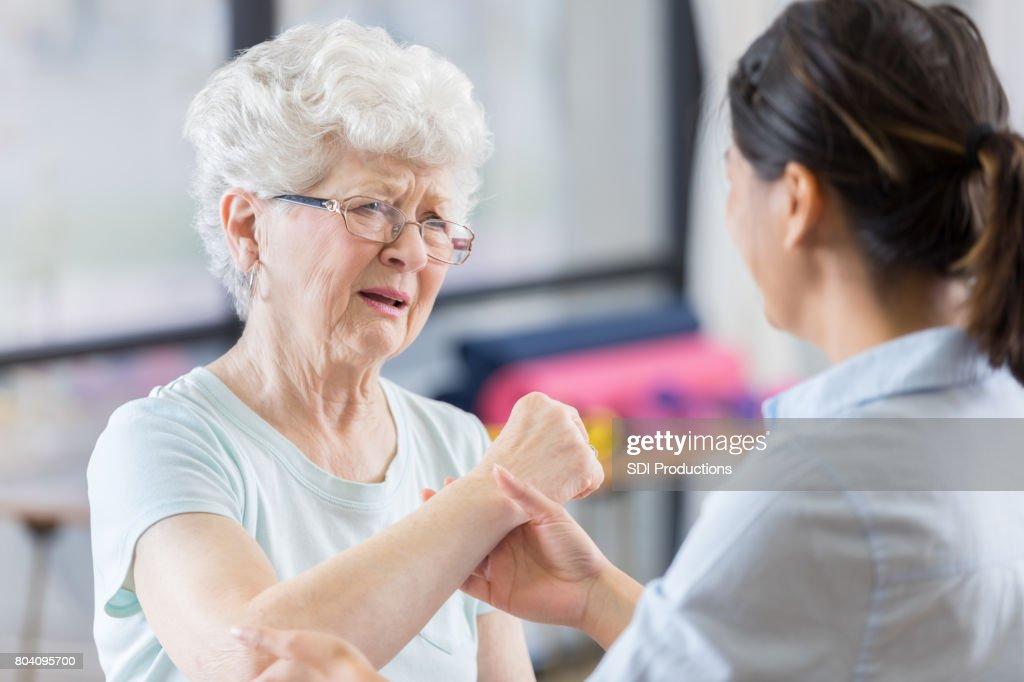 Senior patient grimaces as therapist manipulates elbow : Stock Photo