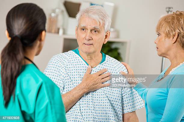 Senior patient in hospital explaining pain to doctor or nurse